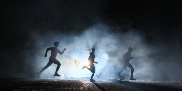 Three runners on foggy road at