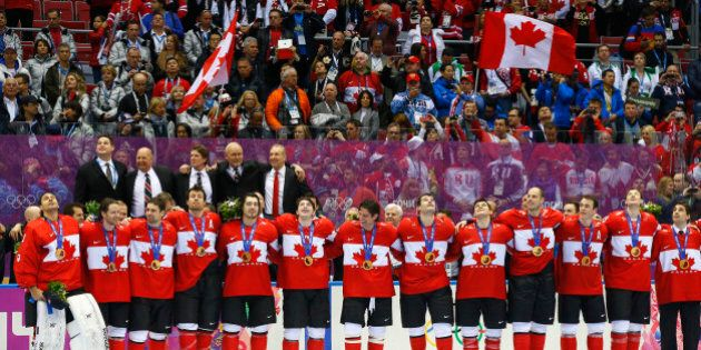 Canada's players sing their national anthem following the medal ceremony after their men's ice hockey...