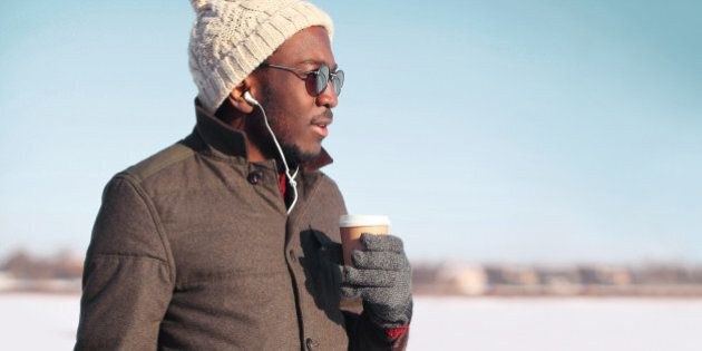 Portrait free young african man enjoying drinking coffee over blue sky in cold winter day looking profile