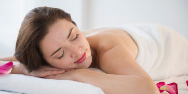 Woman with eyes closed on spa table
