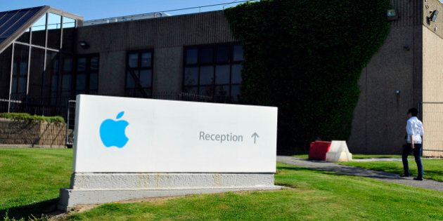 A pedestrian walks near a sign at Apple Inc.'s campus in Cork, Ireland, on Tuesday, June 4, 2013. Speaking...