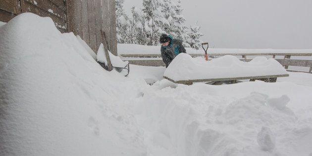 Un employé s'affaire à dégager une terrasse de plus de 50 centimètres de neige mercredi au Mont Sutton en Estrie.
