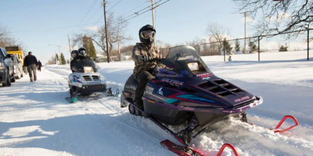 People ride snowmobiles through the streets in Buffalo, New York, November 21, 2014. Warm temperatures and rain were forecast for the weekend in the city of Buffalo and western New York, bringing the threat of widespread flooding to the region bound for days by deep snow. Areas where several feet of snow fell this week should brace for significant, widespread flooding, the National Weather Service warned on Friday. REUTERS/Lindsay DeDario (UNITED STATES - Tags: ENVIRONMENT)