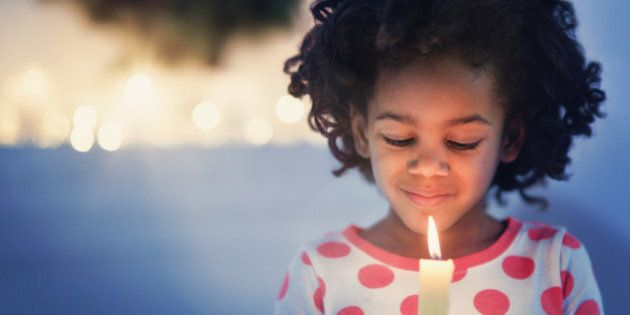 African American girl in pajamas holding lit candle