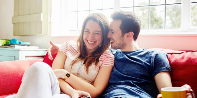 Young couple laugh together as they relax on