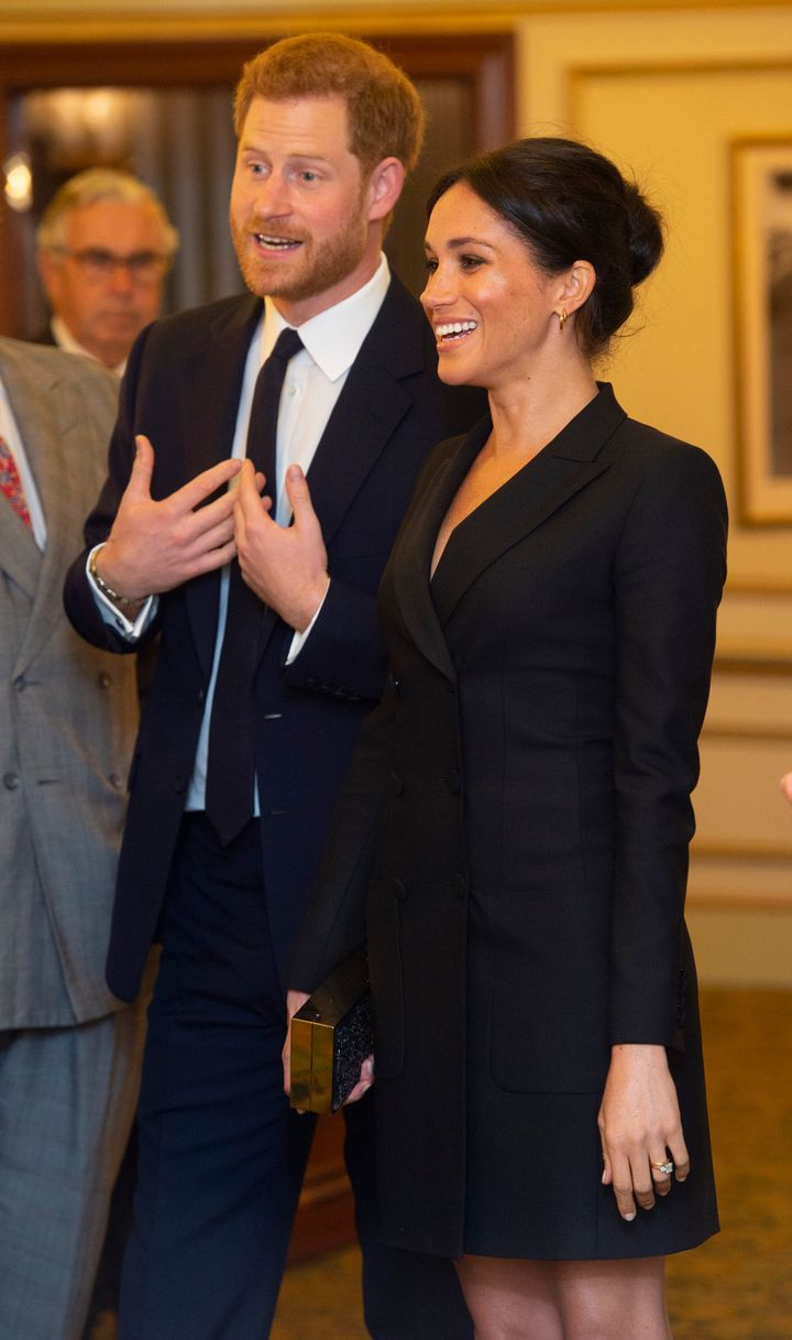 """The Duke and Duchess of Sussex talk with other guests as they attend """"Hamilton"""" in London on August 29, 2018."""
