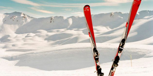Red pair of ski standing in snow.Mountains in