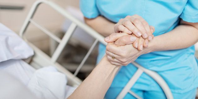 Midsection of female nurse holding senior woman's hand. Caring medical professional is with patient....