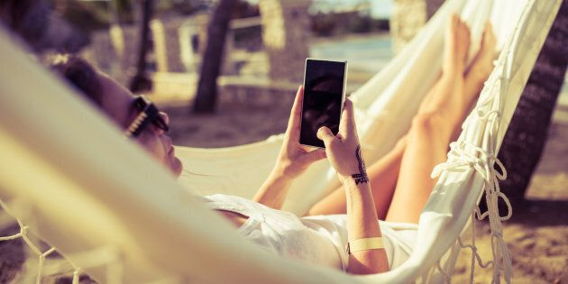 Woman using her phone while relaxing in a hammock by the