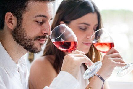 38053331 - close up portrait of young couple at wine tasting. man and woman smelling wine with eyes closed.
