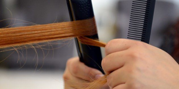 Hairdresser Arzu uses a hair straightener as she dresses a client's hair on August 8, 2012 at the Dry...