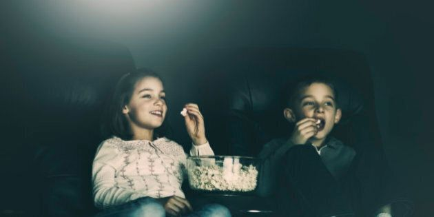 boy and girl, eating popcorn, watching a movie in their home