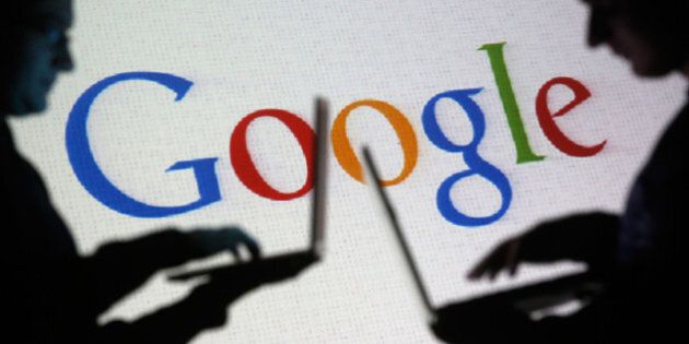 People are silhouetted as they pose with laptops in front of a screen projected with a Google logo, in...