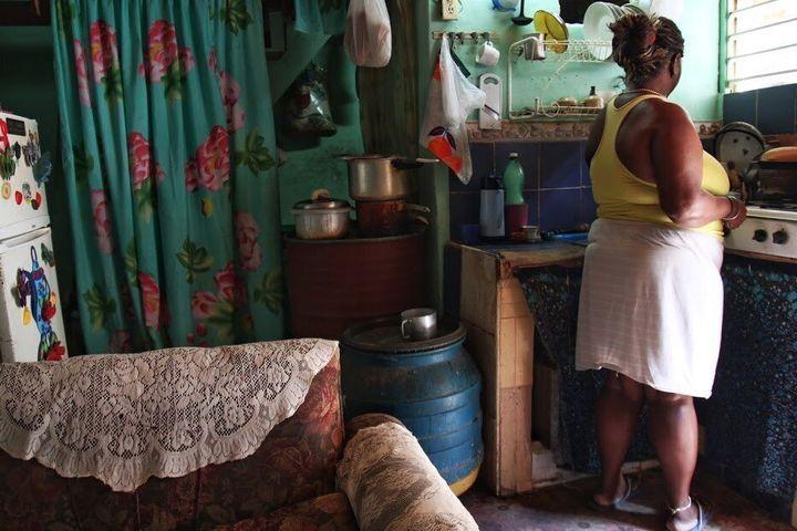 Olivia-mère dans son grand douze pieds par douze pieds, mais avec un deuxième étage de même dimension. Elle termine le lavage de sa vaisselle.