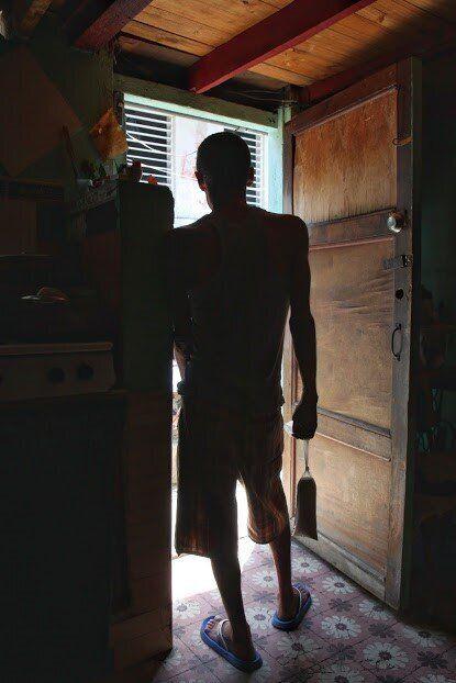 Wilson dans l'embrasure de la porte principale (et la seule) de  son appartement. À la main, un sac de chapelure de pain,  qu'il vend illégalement parce qu'il ne parvient pas à acheter  le permis de vendeur itinérant.