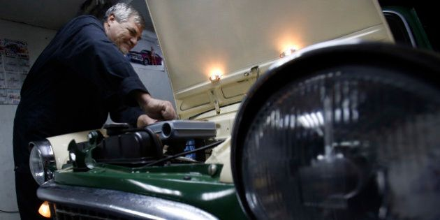 In this file dated Friday, Nov. 28, 2014, Bosnian man Oto Novak works on a Fiat 1100 at his garage, in...