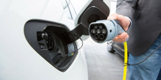 A driver charges a Volkswagen e-Golf electric automobile at a charging station outside the Volkswagen...