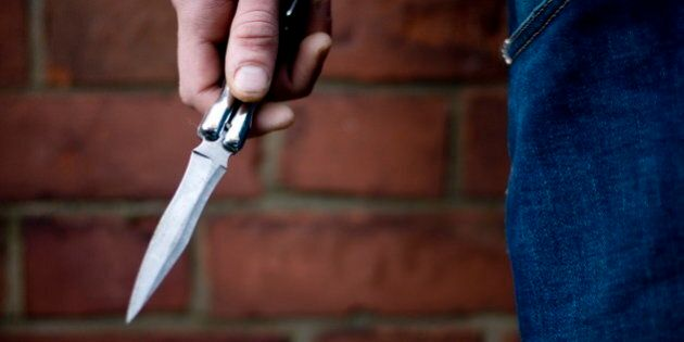 A youth brandishing a knife in the street, UK