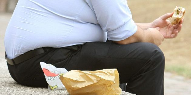 File photo dated 28/07/10 of an overweight man eating, as it was proposed that GPs should be paid to...