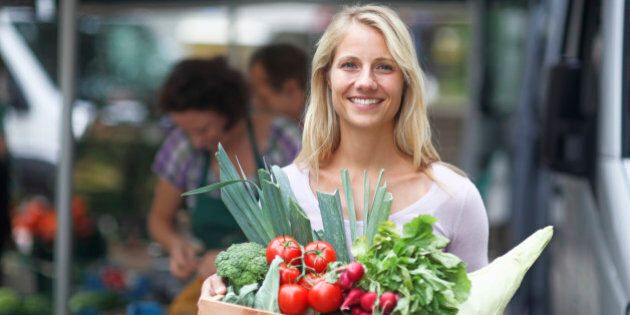 Portrait of mid adult women holding box of vegetables from market