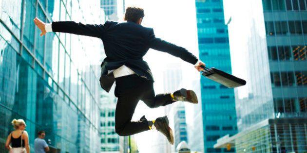 Businessman jumping for joy on city street.