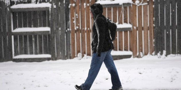 DENVER, CO - November 17: A man walks down a snowy sidewalk along Yale Ave and near Ulster St. November...
