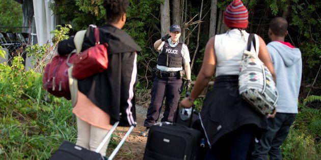 Une agente de la Gendarmerie royale du Canada accueille une famille d'origine haïtienne qui tente d'entrer...
