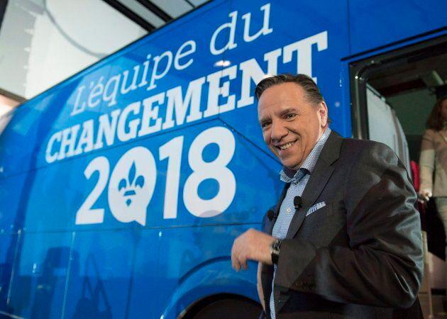 François Legault devant son autobus de campagne (qui était peinturé d'un seul côté).
