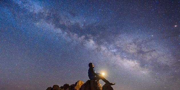 Man sitting under The Milky Way Galaxy with light on his