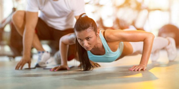 Young woman doing push ups under supervision of a trainer at gym
