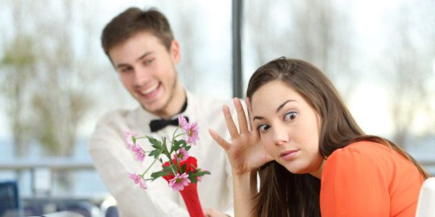 Disgusted woman rejecting a geek boy offering flowers in a blind date in a coffee shop
