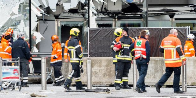 Police and other emergency workers stand in front of the damaged Zaventem Airport terminal in Brussels...
