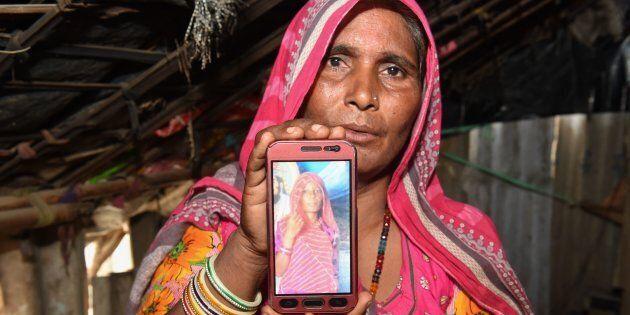 Mohinidevi Nath montre une photo de sa cousinen Shantadevi Nath, qui a été tuée par une bande qui croyait...