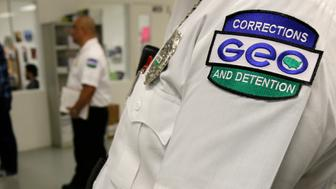 In this photo taken June 21, 2017, an employee of The GEO Group wears a company patch on his uniform as he works at the Northwest Detention Center in Tacoma, Wash., during a media tour. The federal facility, operated under contract by The GEO Group, is used to house people detained on immigration and other violations.(AP Photo/Ted S. Warren)