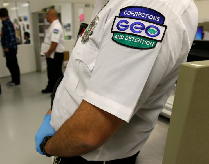 A GEO Group employee wears a company patch on his uniform at the Northwest Detention Center in Tacoma, Wash., during a media