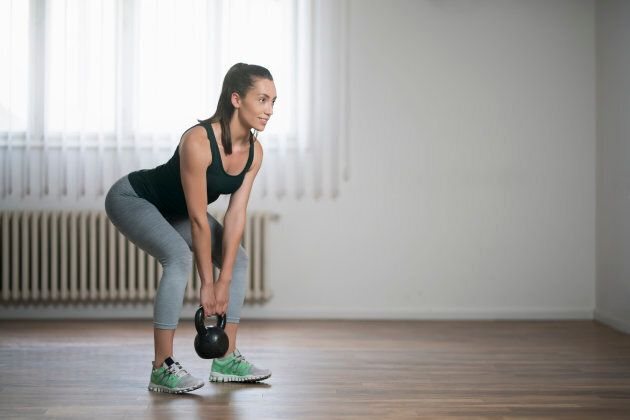 Beautiful young woman doing kettlebell deadlifts at home.