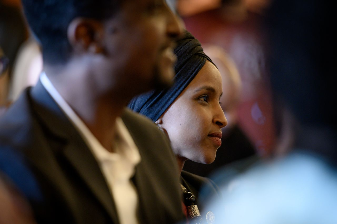 Omar listens to a speaker during the Paycheck Fairness and Women's Workforce Development Town Hall in Minneapolis.