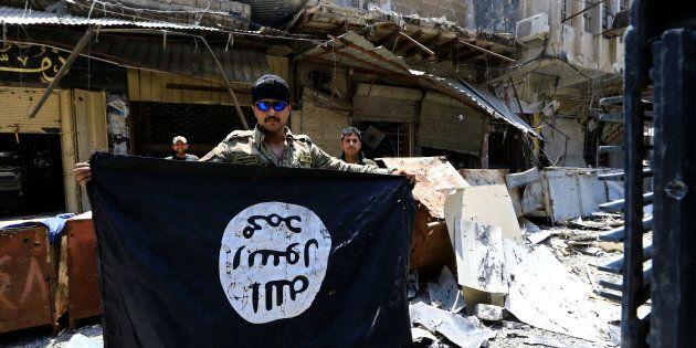 Un membre des forces armées irakienne montre un drapeau de l'État islamique retrouvé à