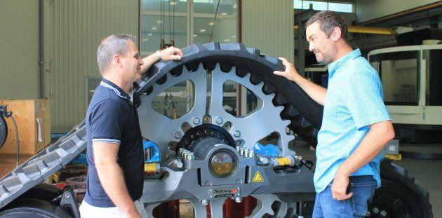Les deux hommes en compagnie d'une chenille pour tracteurs produite dans leur usine.