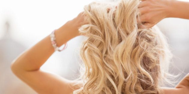 Blonde woman holding her hands in hair. A photo of romantic