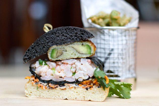 Pain burger à l'encre de seiche et poivre noir, avocat frit, wasabi, sauce soya , crevettes de Matane enveloppées dans des algues de Nori, gingembre frais haché, radis japonais râpé, carotte râpée.