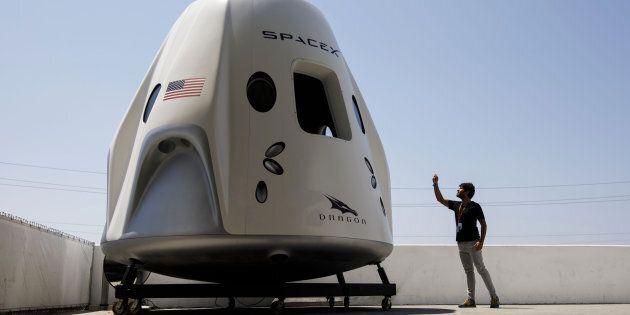 Un visiteur de SpaceX prend en photo une reproduction de la capsule