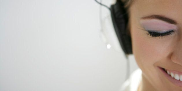 Cropped view of young happy woman listening to