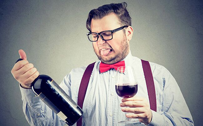 94135884 - man in bowtie trying wine and looking dissatisfied while exploring bottle.