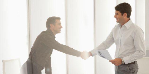 Two businessmen in boardroom shaking hands