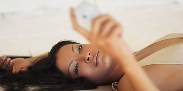 Young woman lying down reading text message