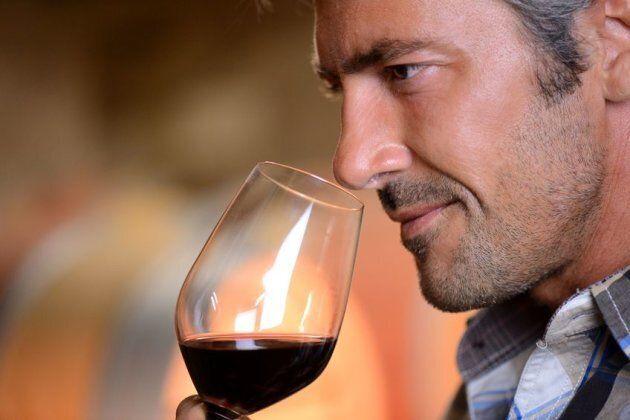 Homme sent verre de vin rouge
