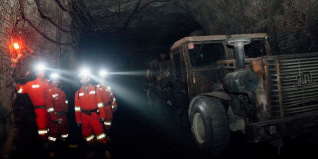 Contractors stand next to a machine while working at the underground Glencore Plc Bracemac-McLeod zinc...