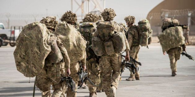 Some of the last British troops head towards the flight line as they prepare to leave Camp Bastion, Helmand...