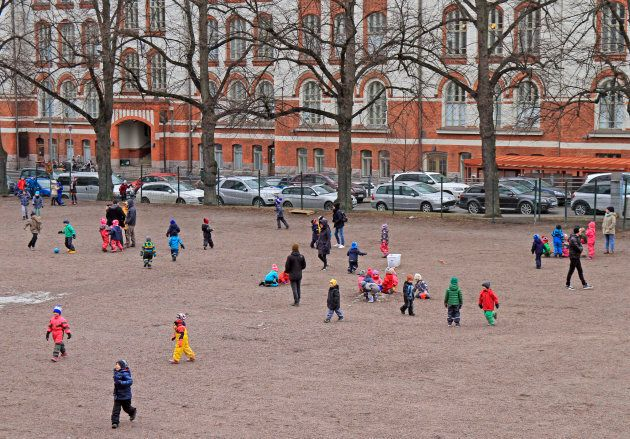 Des enfants jouent dans une cour d'école dehors à Helsinki, en Finlande.